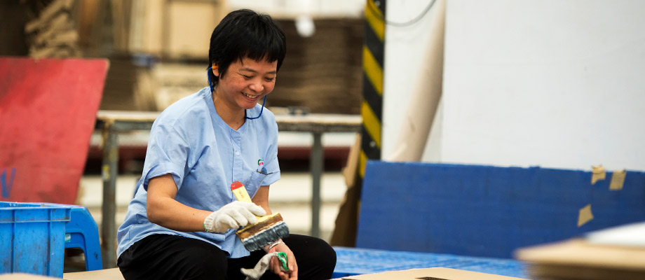 A worker from a Chinese packaging supplier sitting  on the floor holding a paintbrush.
